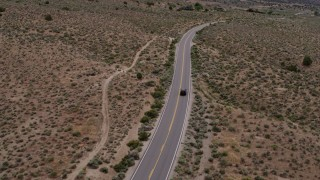 DX0001_000138 - 5.7K stock footage aerial video of a black SUV driving on a lonely desert road in Carson City, Nevada