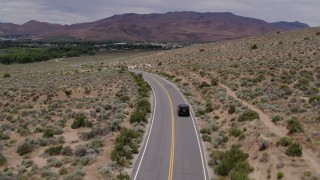 DX0001_000140 - 5.7K stock footage aerial video of a black SUV driving by on a desert road in Carson City, Nevada