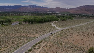 DX0001_000141 - 5.7K stock footage aerial video of a black SUV driving on a desert road in Carson City, Nevada
