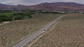 DX0001_000142 - 5.7K stock footage aerial video approach a black SUV driving to the side of the road in Carson City, Nevada