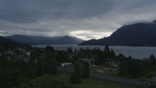 DX0001_000145 - 5.7K stock footage aerial video fly away from the Columbia River and cloud-shrouded mountains at sunrise, Stevenson, Washington