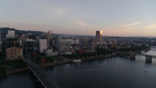 DX0001_000173 - 4K stock footage aerial video flying away from Morrison Bridge and over the Hawthorne Bridge at sunrise, Downtown Portland, Oregon