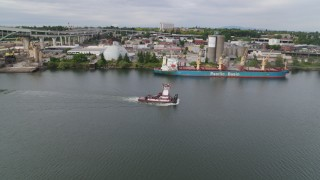 DX0001_000265 - 5.7K stock footage aerial video of tracking tugboat sailing the Willamette River by North Portland, Oregon