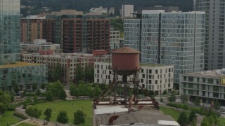 DX0001_000276 - 5.7K stock footage aerial video orbiting an old water tower atop a factory building, sunset, Downtown Portland, Oregon