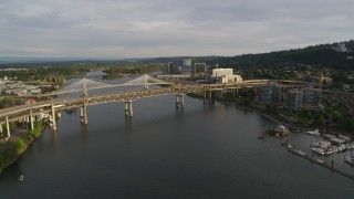 DX0001_000294 - 5.7K stock footage aerial video reverse over river from bridges, revealing marina, sunset, South Portland, Oregon