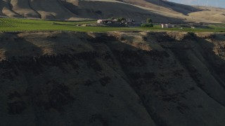 DX0001_000498 - 5.7K stock footage aerial video fly over cliff and vineyard toward the Maryhill Winery in Goldendale, Washington
