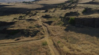 DX0001_000501 - 5.7K stock footage aerial video of ascending beside a dirt road to reveal Lewis and Clark Highway in Goldendale, Washington
