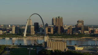 DX0001_000514 - 5.7K stock footage aerial video passing by a grain elevator and casino against The Arch and skyline at sunrise, Downtown St. Louis, Missouri