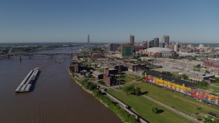 DX0001_000582 - 5.7K stock footage aerial video of barges in the Mississippi River near riverfront buildings, Downtown St. Louis, Missouri