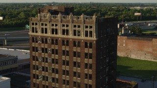 DX0001_000673 - 5.7K stock footage aerial video of approaching the abandoned office building at sunset in East St. Louis, Illinois