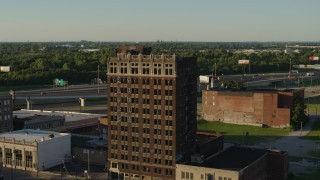 DX0001_000676 - 5.7K stock footage aerial video a stationary view of an abandoned office building at sunset in East St. Louis, Illinois