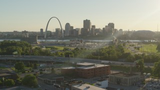 DX0001_000679 - 5.7K stock footage aerial video fly over brick building at sunset toward Gateway Arch and Downtown St. Louis, Missouri