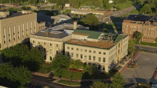 DX0001_000686 - 5.7K stock footage aerial video of orbiting the side of a federal courthouse at sunset in East St. Louis, Illinois