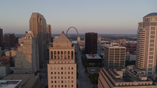 DX0001_000868 - 5.7K stock footage aerial video of a static then reverse view of the Arch seen over a courthouse at sunset, Downtown St. Louis, Missouri