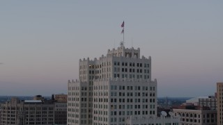 DX0001_000886 - 5.7K stock footage aerial video of flags atop a downtown apartment building at twilight, Downtown St. Louis, Missouri