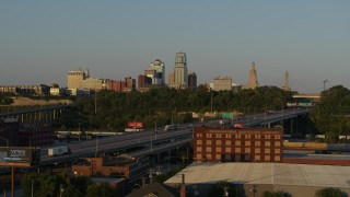 DX0001_001166 - 5.7K stock footage aerial video flying by freeway with light traffic with view of skyline at sunset in Downtown Kansas City, Missouri
