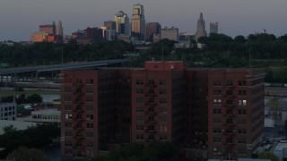 DX0001_001184 - 5.7K stock footage aerial video orbit brick office building at twilight, skyline in background, Kansas City, Missouri