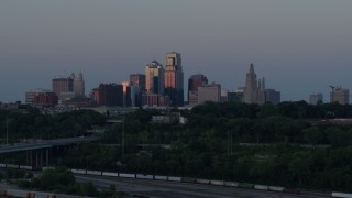 DX0001_001191 - 5.7K stock footage aerial video passing the city's skyline lit by the setting sun in Downtown Kansas City, Missouri, twilight