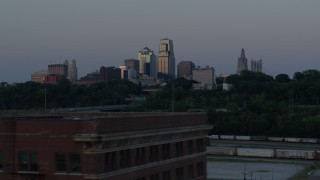 DX0001_001194 - 5.7K stock footage aerial video of the city skyline at twilight while descending to reveal brick building, Downtown Kansas City, Missouri