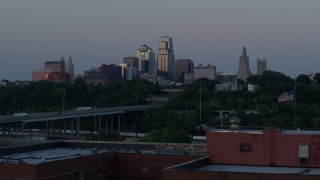 DX0001_001197 - 5.7K stock footage aerial video of city skyline while descending by brick building at twilight, Downtown Kansas City, Missouri