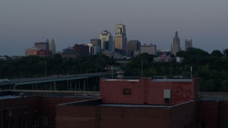 DX0001_001199 - 5.7K stock footage aerial video of the skyline at twilight, descend to reveal brick building, Downtown Kansas City, Missouri