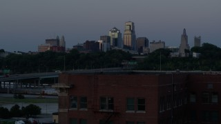 DX0001_001203 - 5.7K stock footage aerial video descend with view of skyline at twilight, reveal brick building, Downtown Kansas City, Missouri