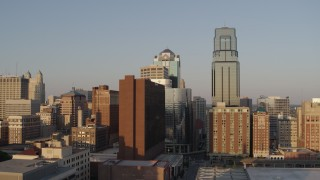 DX0001_001347 - 5.7K stock footage aerial video of the setting sun shining on city skyscrapers in Downtown Kansas City, Missouri