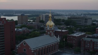DX0001_001361 - 5.7K stock footage aerial video of circling a brick cathedral's steeple at sunset in Downtown Kansas City, Missouri
