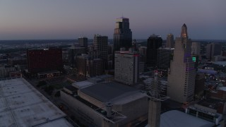 DX0001_001385 - 5.7K stock footage aerial video static view of city skyscrapers lit up for the evening at twilight in Downtown Kansas City, Missouri