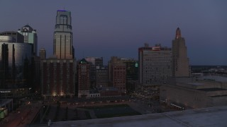 DX0001_001392 - 5.7K stock footage aerial video a view of a downtown hotel between skyscrapers at twilight in Downtown Kansas City, Missouri