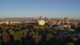 DX0001_001410 - 5.7K stock footage aerial video ascend near apartment buildings for view of skyscrapers in Downtown Denver, Colorado at sunrise