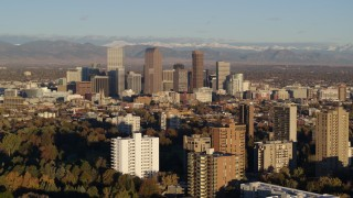 DX0001_001418 - 5.7K stock footage aerial video of tall skyscrapers in Downtown Denver, Colorado at sunrise, seen while ascending near apartment buildings
