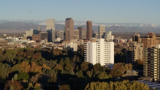 DX0001_001421 - 5.7K stock footage aerial video descend near apartment building with view of skyscrapers in Downtown Denver, Colorado at sunrise