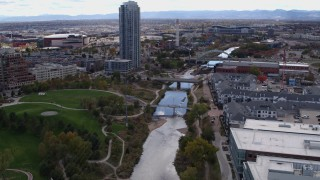 DX0001_001501 - 5.7K stock footage aerial video fly over South Platte River to approach bridges and skyscraper in Downtown Denver, Colorado
