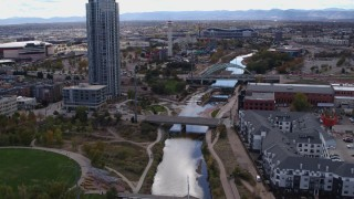 DX0001_001502 - 5.7K stock footage aerial video follow South Platte River to approach bridges and skyscraper in Downtown Denver, Colorado