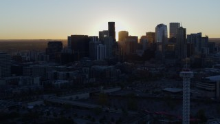 DX0001_001614 - 5.7K stock footage aerial video of the sun behind the city skyline at sunrise in Downtown Denver, Colorado