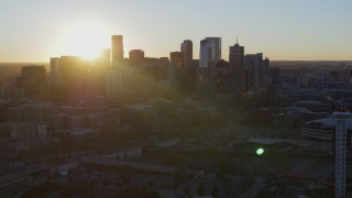 DX0001_001615 - 5.7K stock footage aerial video of the rising sun behind the city skyline at sunrise in Downtown Denver, Colorado