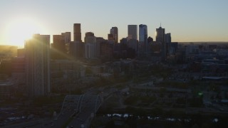 DX0001_001616 - 5.7K stock footage aerial video descend with view of the sun behind the city skyline at sunrise in Downtown Denver, Colorado