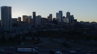 DX0001_001620 - 5.7K stock footage aerial video descend with view of bright sun and city skyline at sunrise in Downtown Denver, Colorado