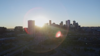 DX0001_001621 - 5.7K stock footage aerial video ascend for stationary view of bright sun and city skyline at sunrise in Downtown Denver, Colorado