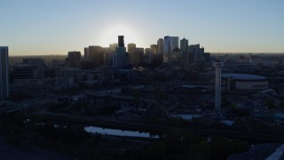 DX0001_001622 - 5.7K stock footage aerial video flyby bright sun and city skyline, seen from theme park and arena at sunrise in Downtown Denver, Colorado