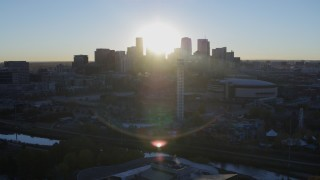 DX0001_001623 - 5.7K stock footage aerial video of sun and city skyline, seen from theme park and arena at sunrise in Downtown Denver, Colorado