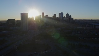 DX0001_001625 - 5.7K stock footage aerial video of sun and city skyline, seen while flying by skyscraper at sunrise in Downtown Denver, Colorado