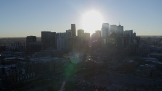 DX0001_001627 - 5.7K stock footage aerial video of the rising sun behind the city skyline in Downtown Denver, Colorado