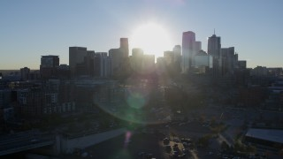 DX0001_001629 - 5.7K stock footage aerial video of passing the rising sun behind the city skyline in Downtown Denver, Colorado