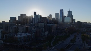 DX0001_001630 - 5.7K stock footage aerial video flyby the rising sun behind the city skyline in Downtown Denver, Colorado