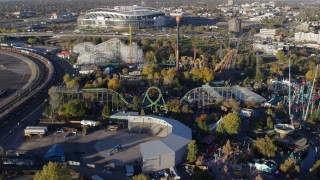 DX0001_001635 - 5.7K stock footage aerial video reverse view of rides at Elitch Gardens at sunrise in Downtown Denver, Colorado