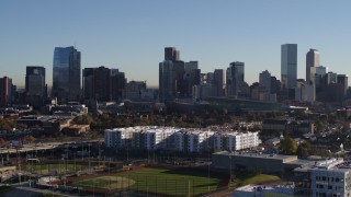 DX0001_001646 - 5.7K stock footage aerial video ascend to focus on the city's skyline at sunrise in Downtown Denver, Colorado