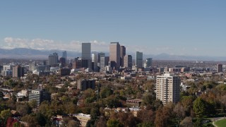 DX0001_001732 - 5.7K stock footage aerial video ascend to wider view of the city's skyline, seen from park with trees, Downtown Denver, Colorado