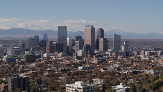 DX0001_001740 - 5.7K stock footage aerial video slow descent by the city's skyline with mountains in background, Downtown Denver, Colorado